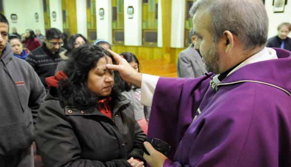 El Padre Ricardo Quiñones impone la ceniza.
